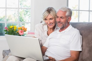 attractive retiree couple using laptop at home on couch