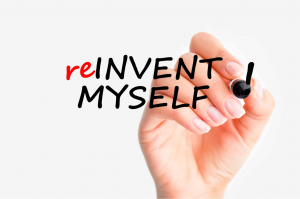 """Hand with lady's hand writing """"reinvent myself"""""""