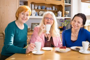 Happy mature women at table drinking coffee